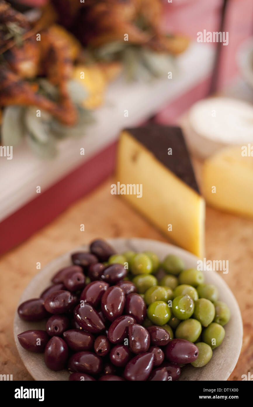 A buffet table laid out for a party Organic food A cheese board selection and a plate of green and black olives - Stock Image