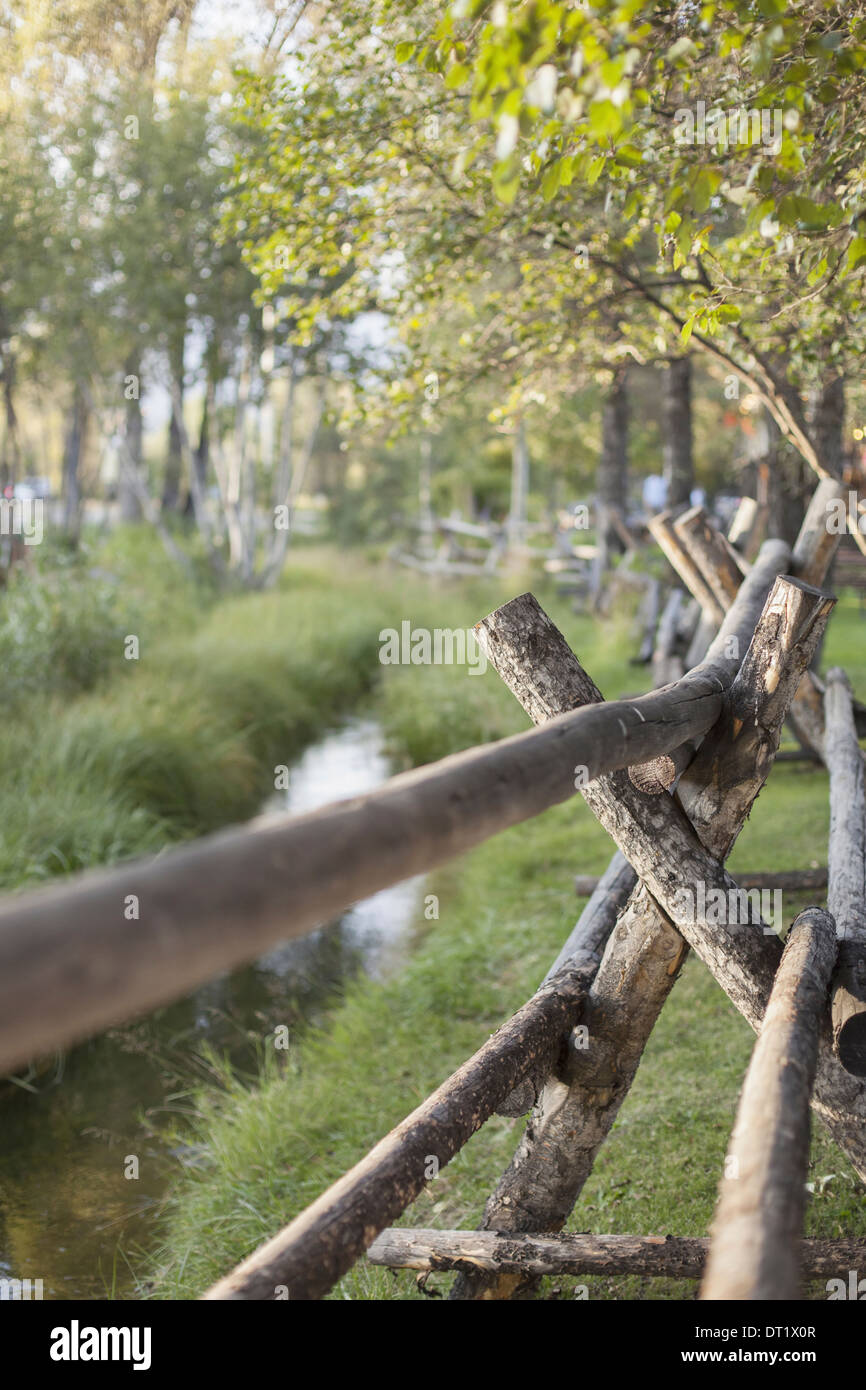 A rural scene view over a fence made of wooden posts A small stream Trees with vivid green leaves - Stock Image