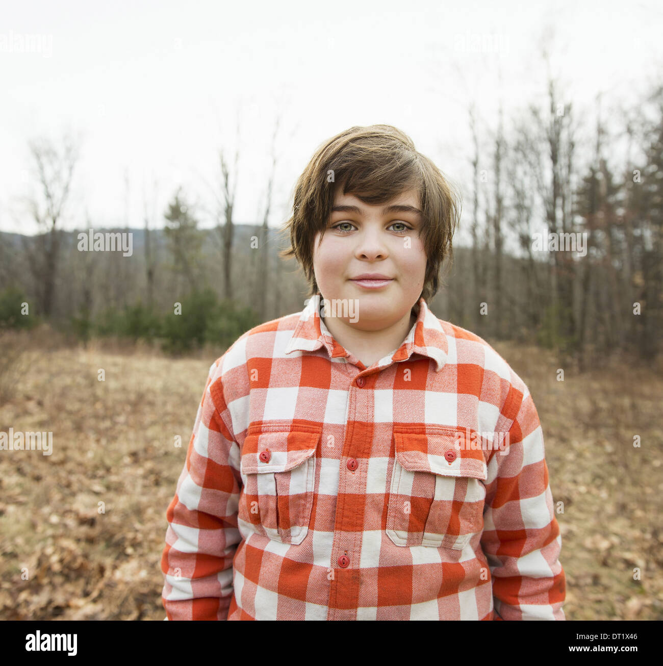 A young boy in a red checked shirt outside on a winter's day - Stock Image