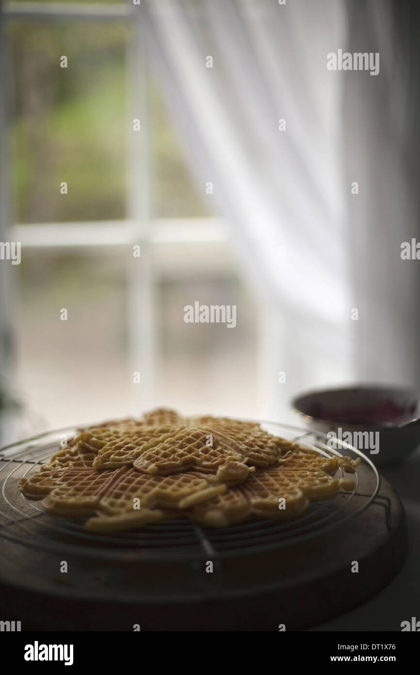 A dish of waffles on a tabletop Net curtains draped back from a window - Stock Image