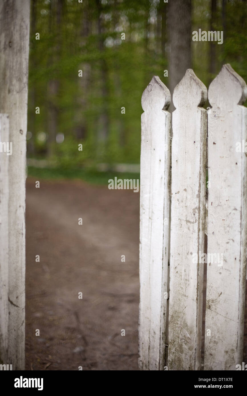 A white picket fence with an open garden gate - Stock Image