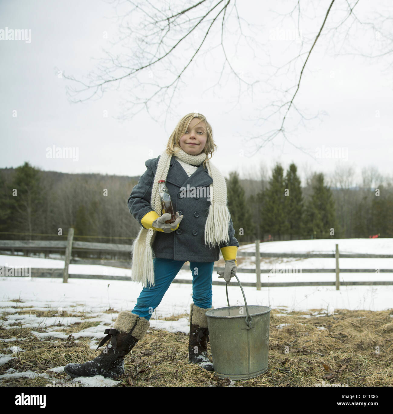 A girl in the snow carrying a metal bucket - Stock Image