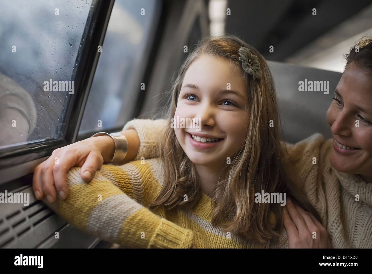 A man and a young girl sitting beside the window in a train carriage looking out at the countryside Smiling in excitement - Stock Image
