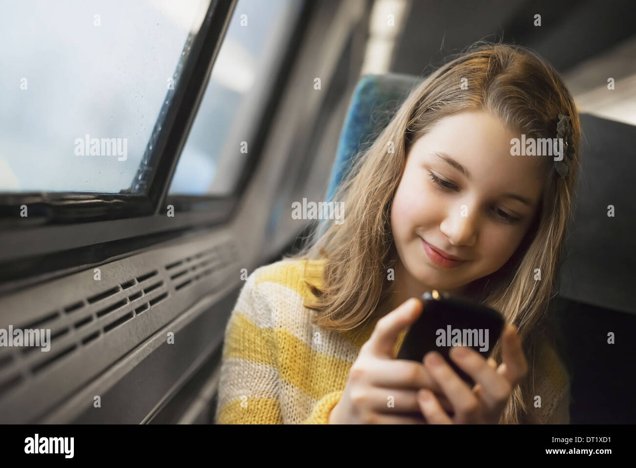 A young girl with long blonde hair sitting by a window on a train using her mobile phone texting and sending messages - Stock Image