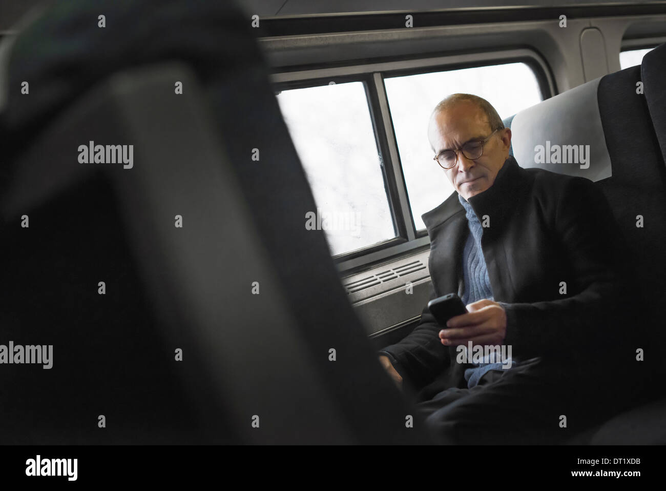 A mature man sitting by a window in a train carriage using his mobile phone keeping in touch on the move - Stock Image