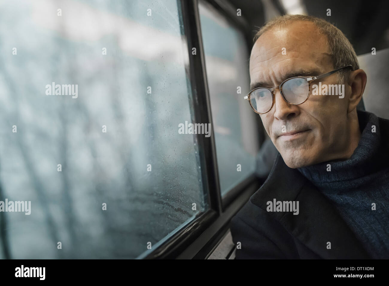 A mature man sitting in a window seat on a train journey looking out into the distance - Stock Image
