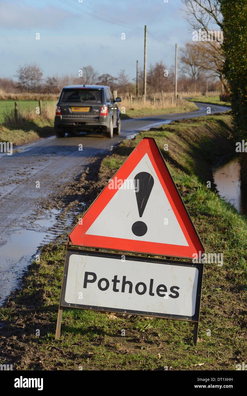 four wheel drive vehicle passing warning sign of potholes on country road yorkshire united kingdom - Stock Image