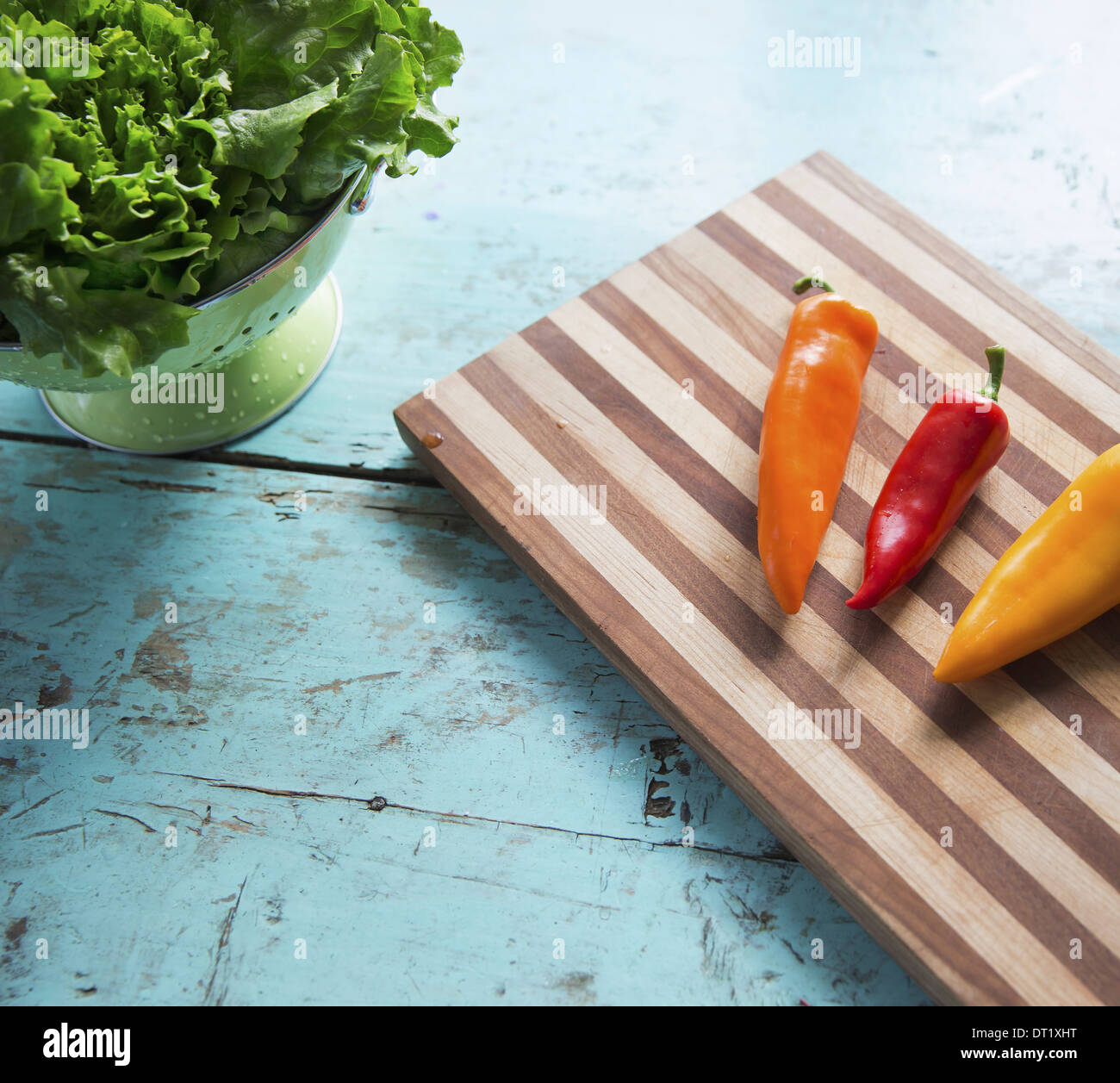 A tabletop with a wooden chopping board and three sweet peppers and a bowl of salad leaves Stock Photo