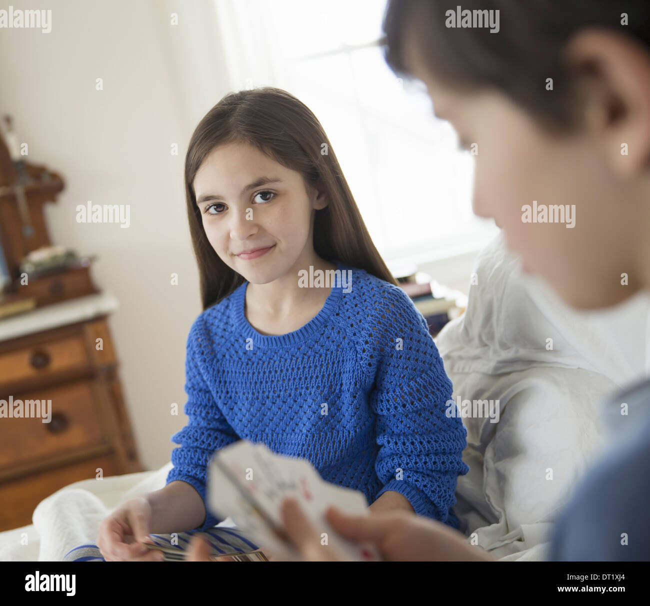 Two children at home sitting side by side and playing a game of cards - Stock Image