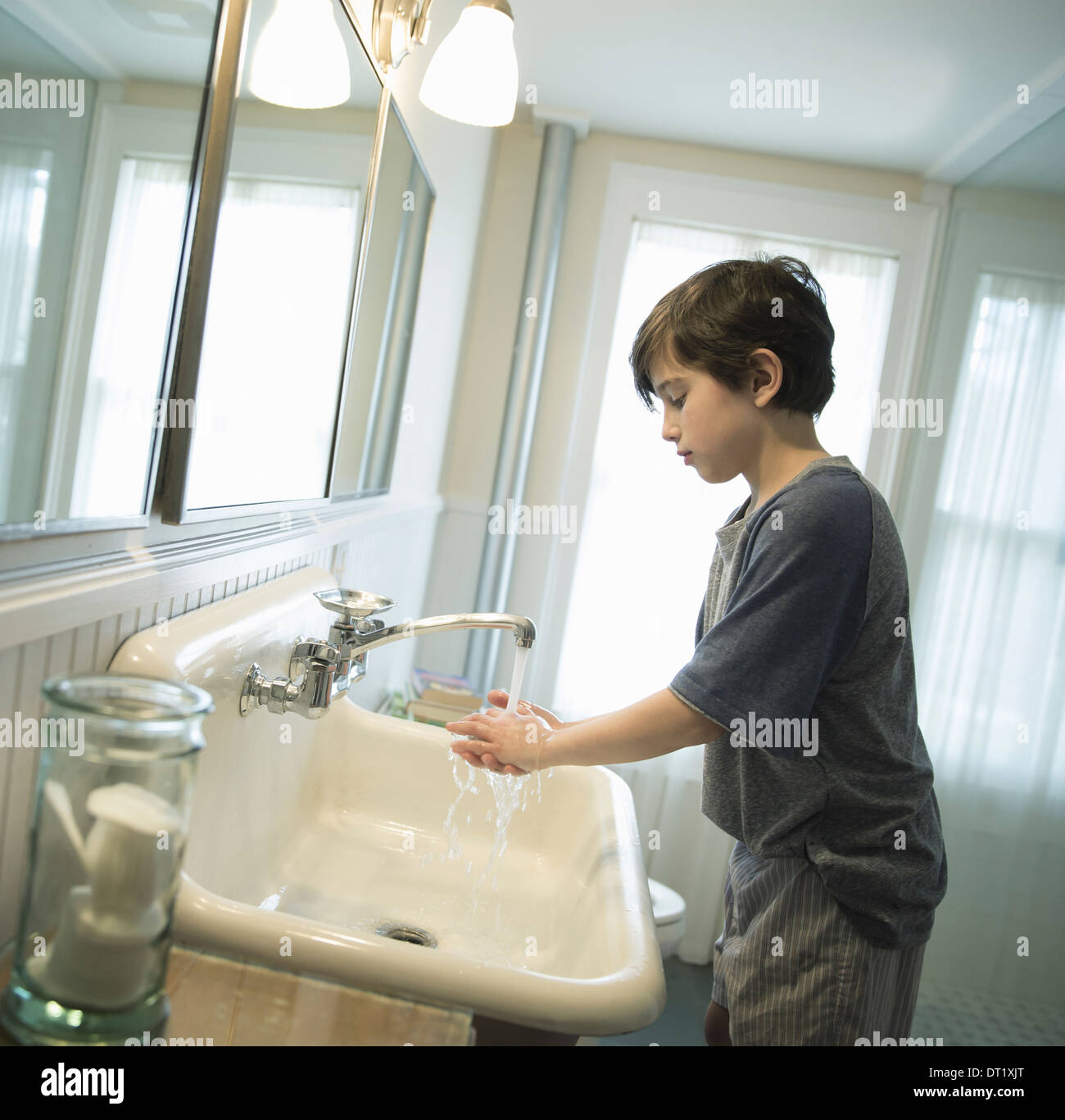 A boy standing in the bathroom washing his hands under the tap - Stock Image