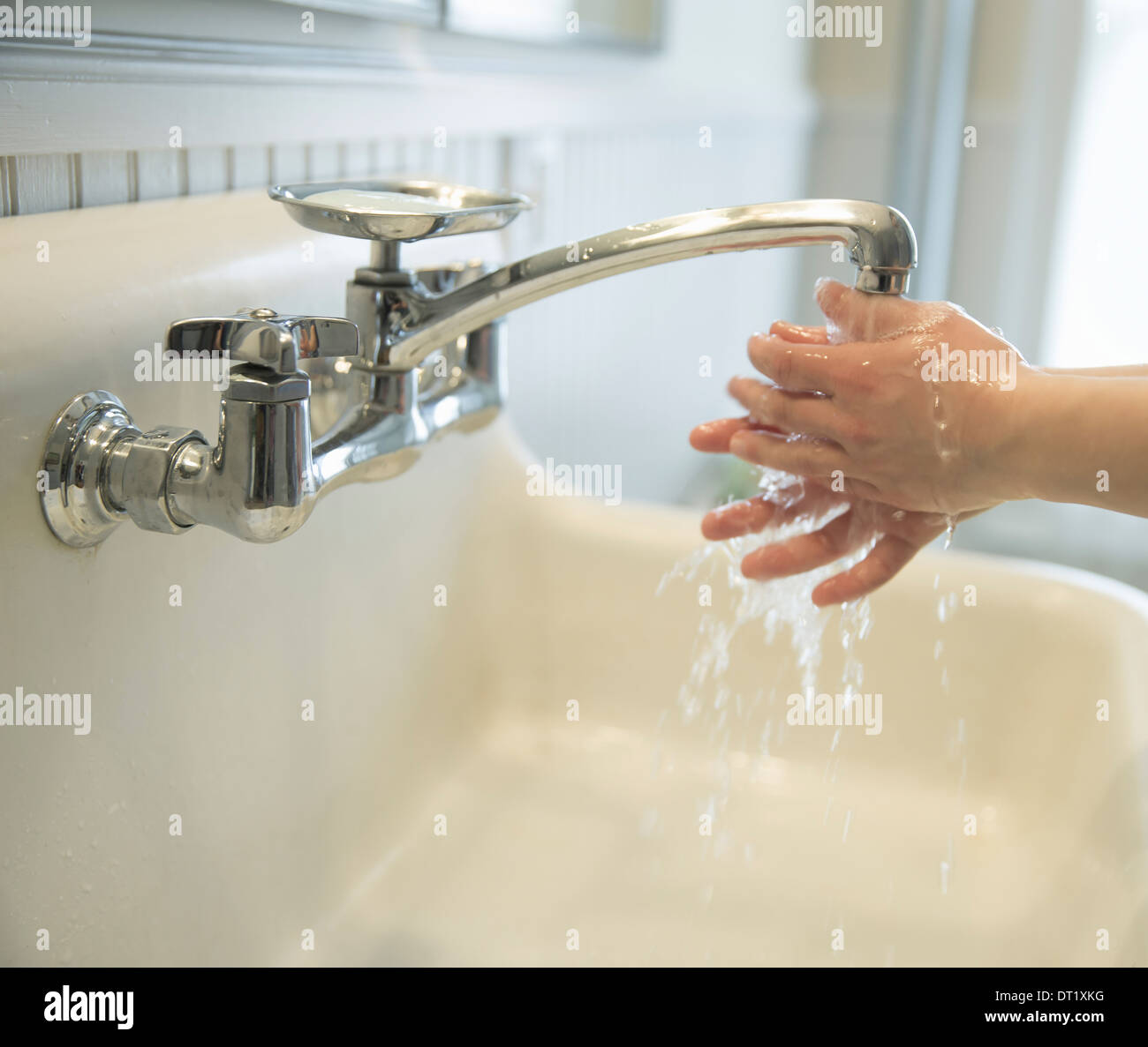 A boy washing his hands under the bathroom tap - Stock Image