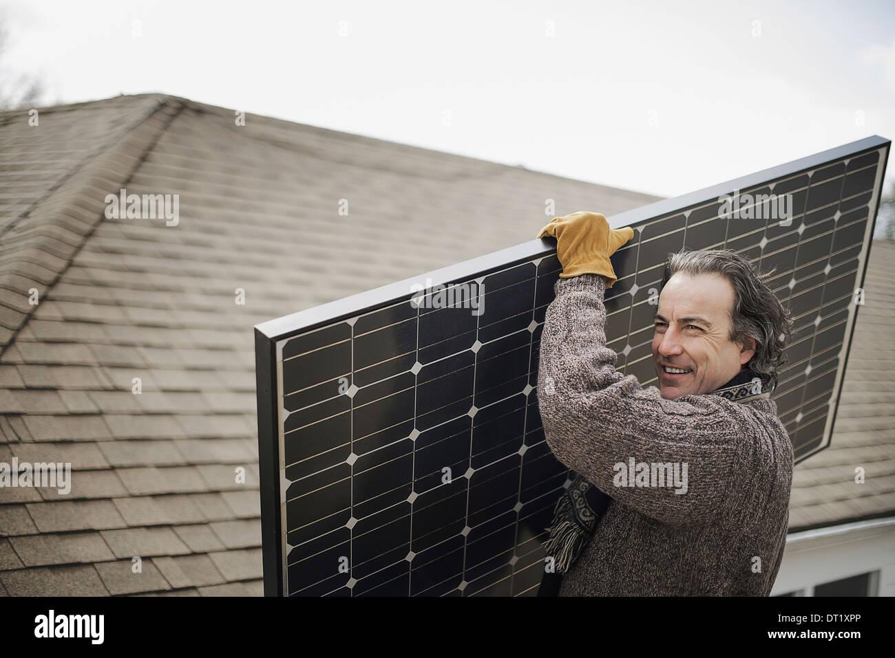 A man carrying a large solar panel across a farmyard - Stock Image