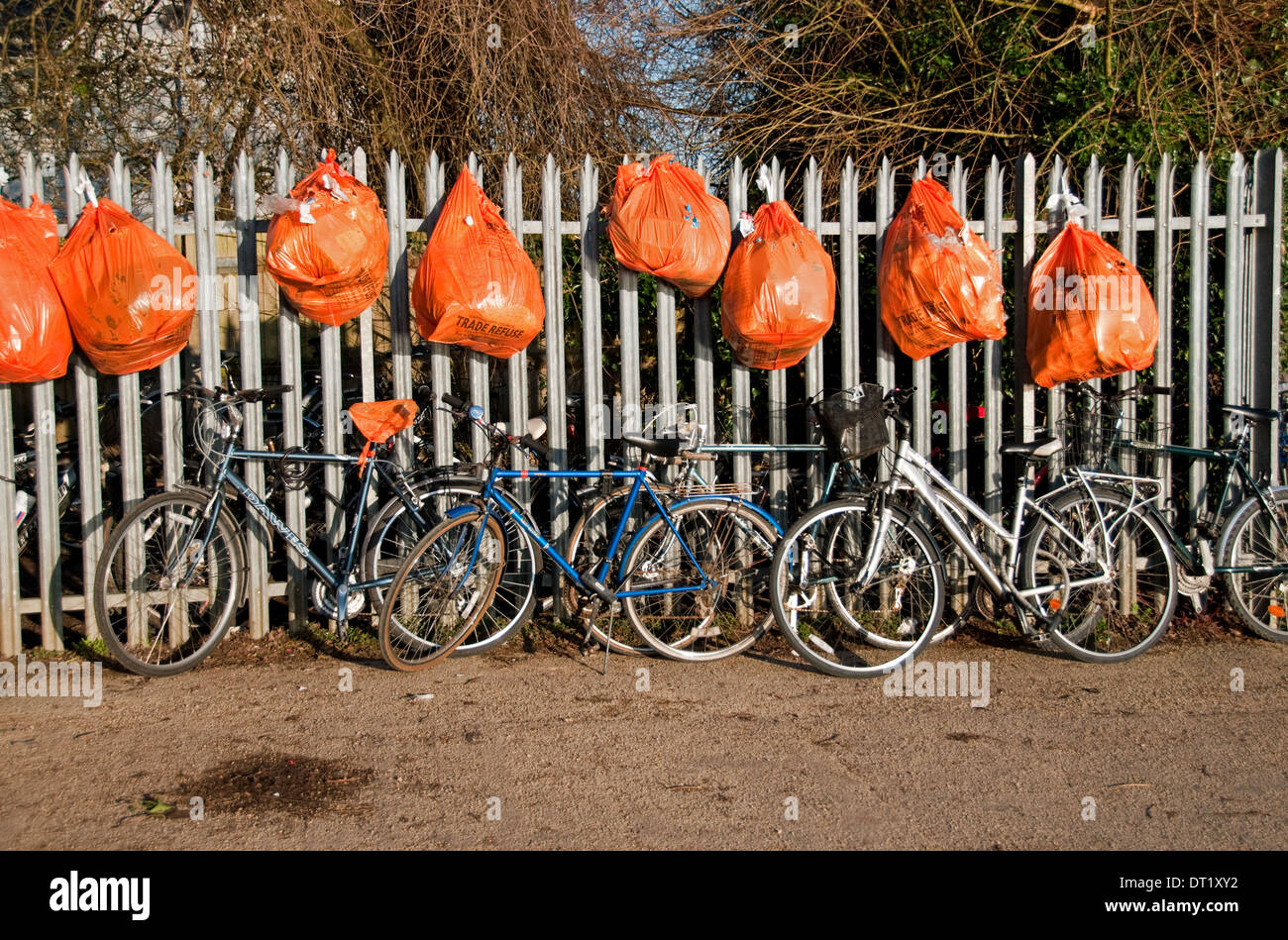 Rubbish Bags Fence and bicycles - Stock Image