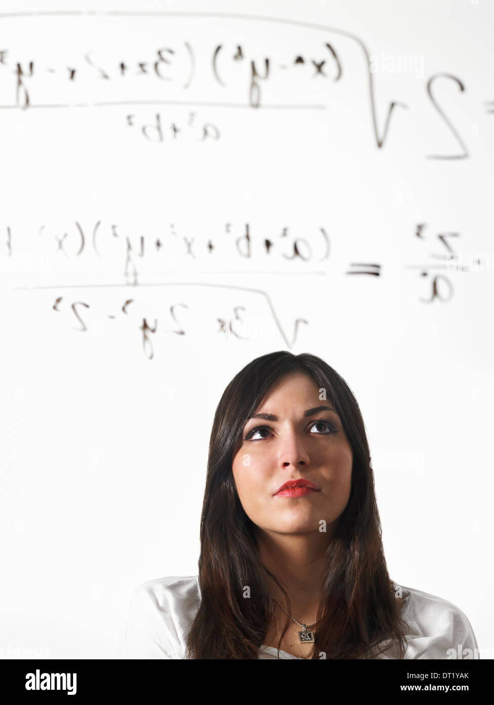 A young woman writing a mathematical equation with black marker on a clear see-through surface and standing back to consider it - Stock Image