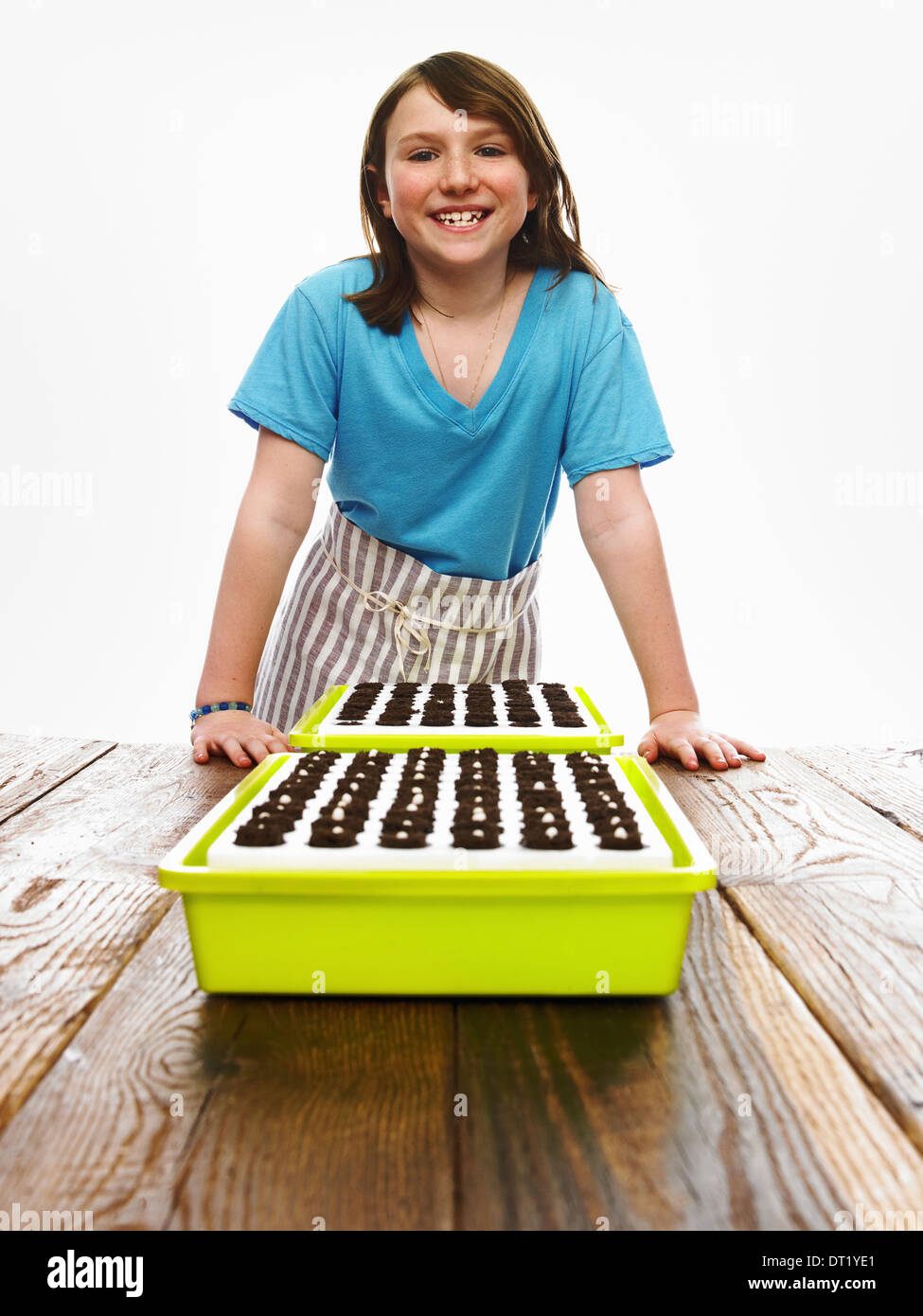 A young girl leaning on a table with two tray of freshly planted seeds resting on dark organic soil - Stock Image