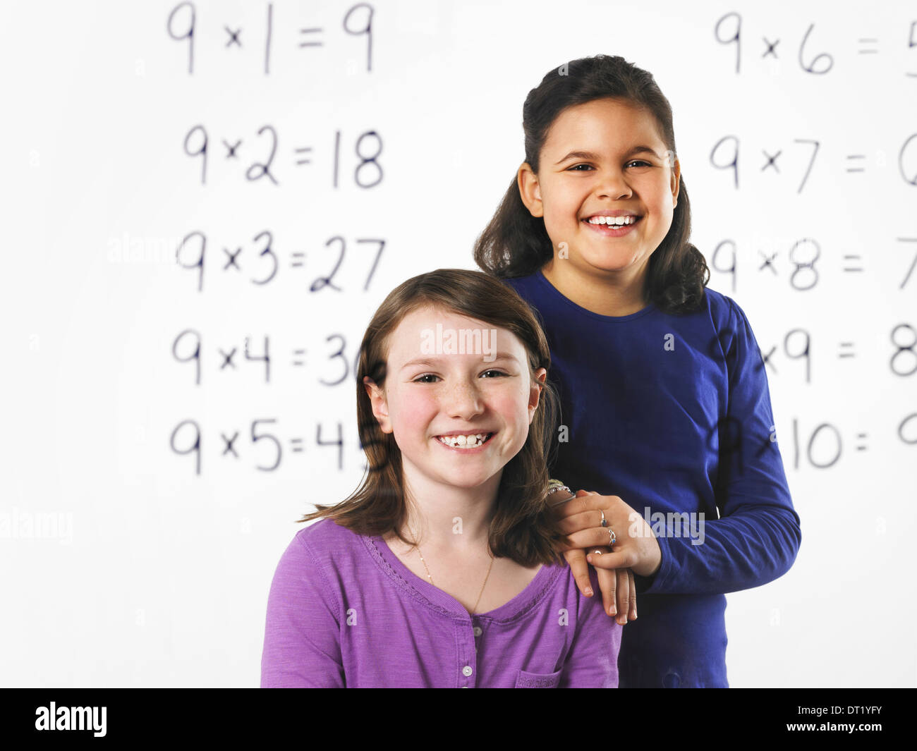 Two girls looking at a series of mathematical multiplication tables on a see through clear wall with black pen Learning - Stock Image