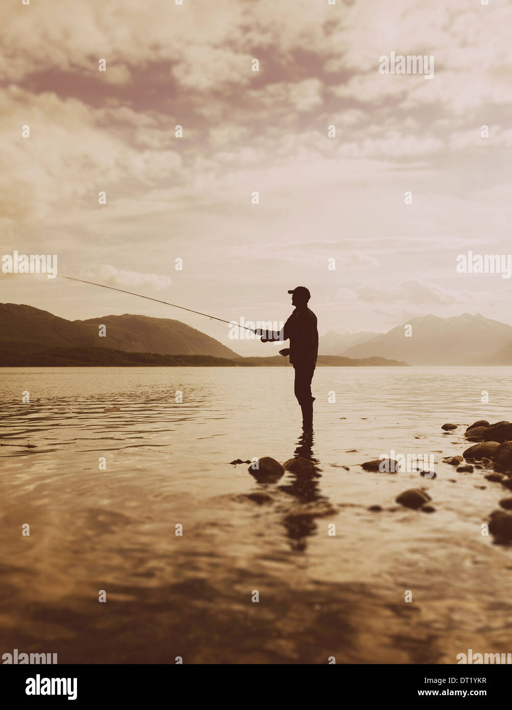 Silhouette of a man fly-fishing in calm waters on the Waschusett inlet in Glacier Bay national park in Alaska Stock Photo