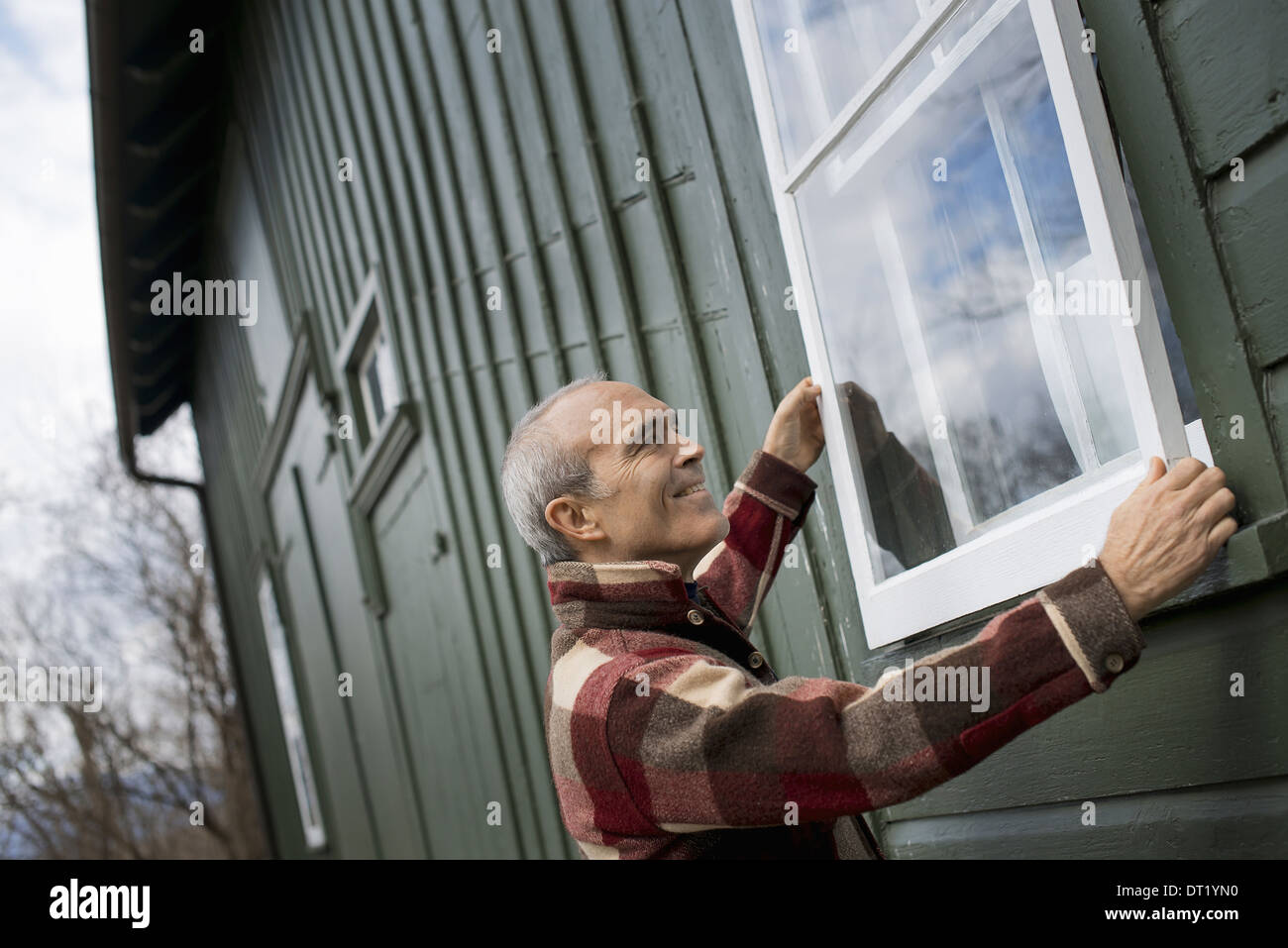 An organic farm in winter Maintenance A man holding a storm window panel against the window frame - Stock Image