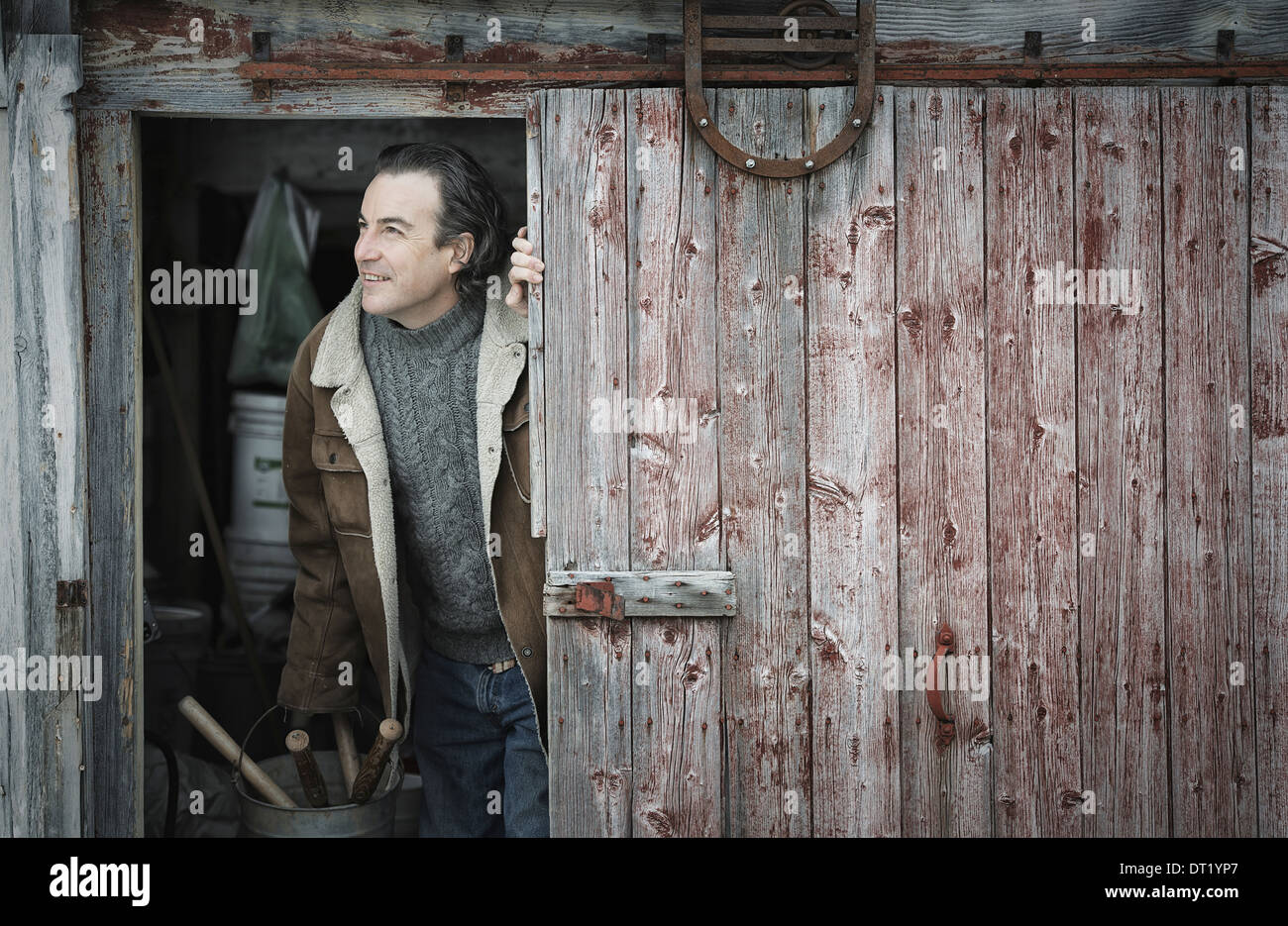 An organic farm in upstate New York in winter A man at an open barn door - Stock Image