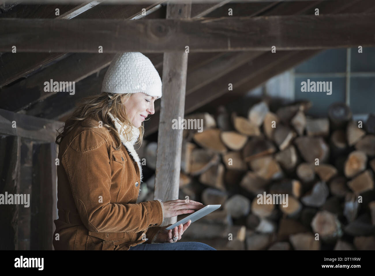 An organic farm in upstate New York in winter A woman sitting in an outbuilding using a digital tablet - Stock Image