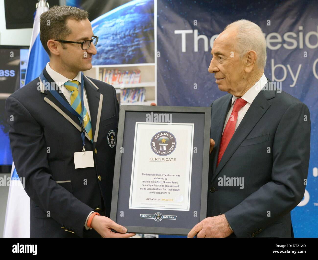 (140206) -- NETANYA (ISRAEL), Feb. 6, 2014 (Xinhua) -- Israeli President Shimon Peres (R) receives a certificate of the Guinness World Record for the largest online civics lesson from Guinness World Records Senior Vice President Marco Frigatti (L) in the Cisco headquarters in Netanya, Israel, on Feb. 6, 2014. Peres and over 9000 high school students across Israel, using Cisco Systems Telepresence technology, broke the Guinness World Record for the largest online civics lesson. Over 8500 students heard Peres live and some had the opportunity to ask him questions. (Xinhua/GPO/Mark Neyman) - Stock Image