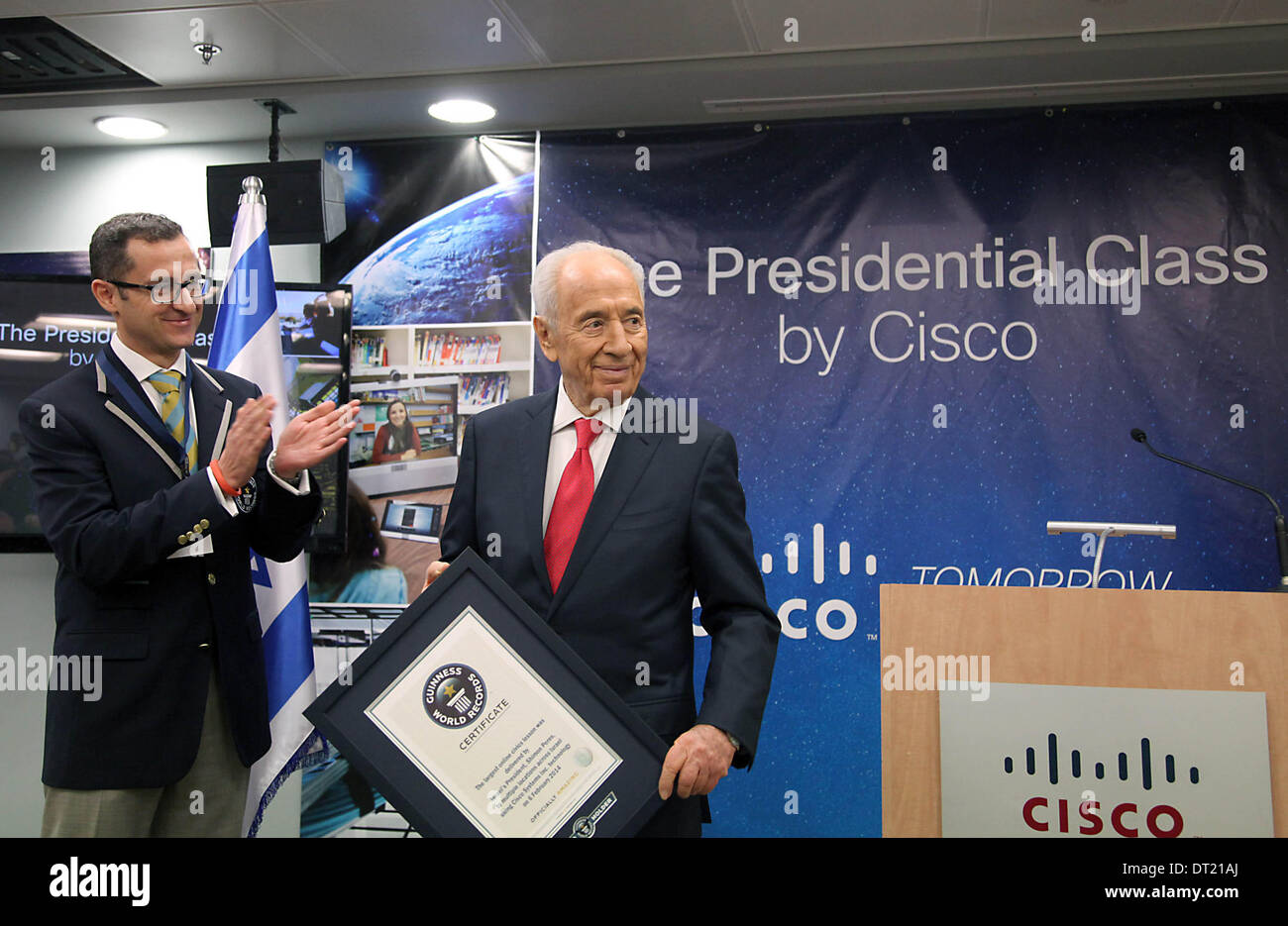 (140206) -- NETANYA (ISRAEL), Feb. 6, 2014 (Xinhua) -- Israeli President Shimon Peres (R) receives a certificate of the Guinness World Record for the largest online civics lesson from Guinness World Records Senior Vice President Marco Frigatti (L) in the Cisco headquarters in Netanya, Israel, on Feb. 6, 2014. Peres and over 9000 high school students across Israel, using Cisco Systems Telepresence technology, broke the Guinness World Record for the largest online civics lesson. Over 8500 students heard Peres live and some had the opportunity to ask him questions. (Xinhua/JINI/Gidon Markovitz) - Stock Image