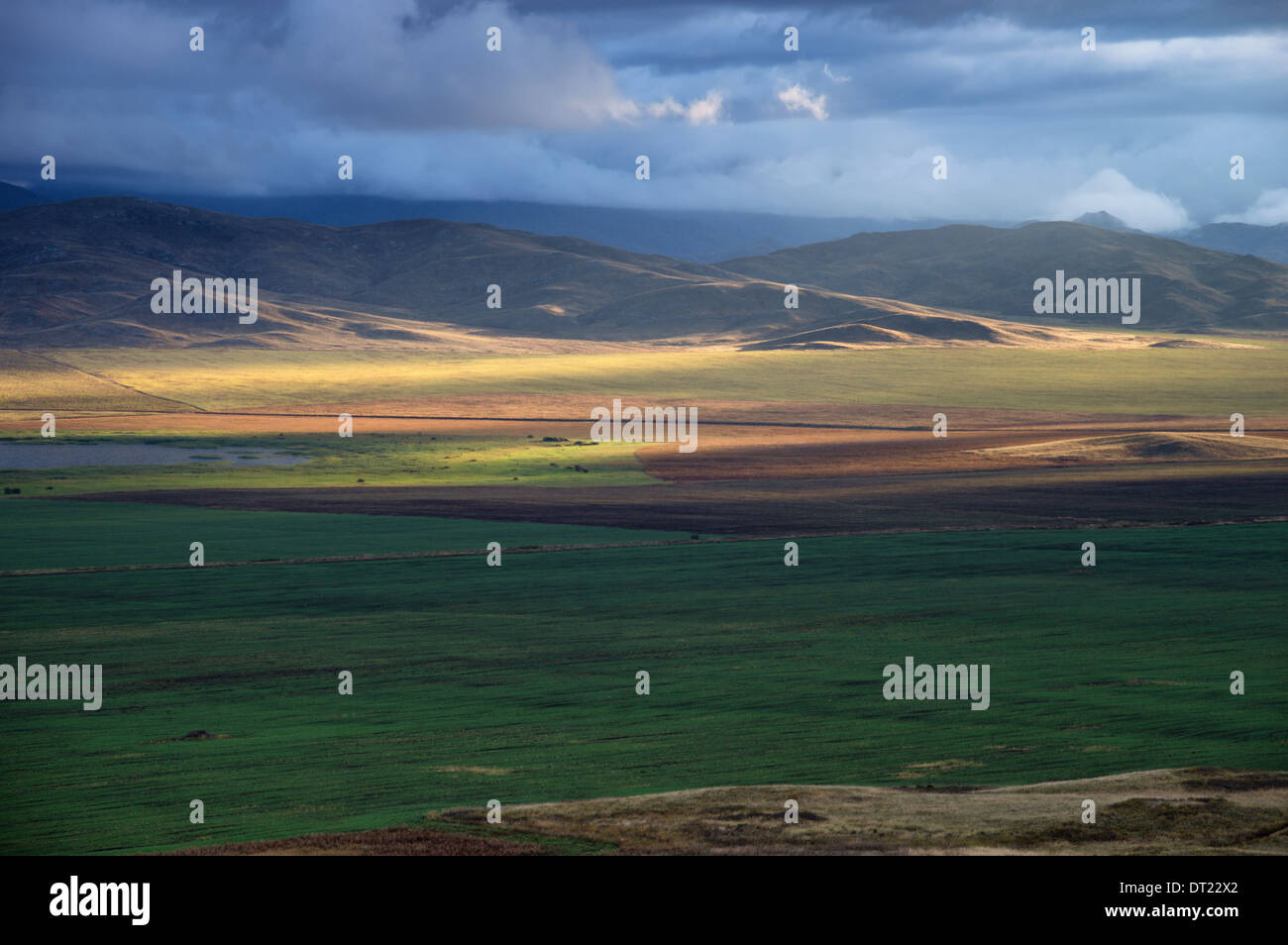 Storm sky and sun gaps on the fields and hills on the horizon - Stock Image