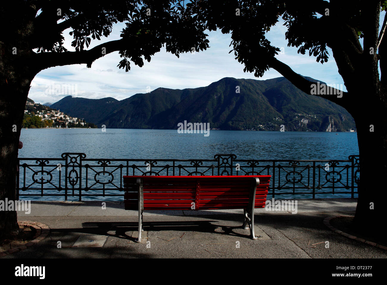 A red bench between two trees in front of Lugano lake - Stock Image