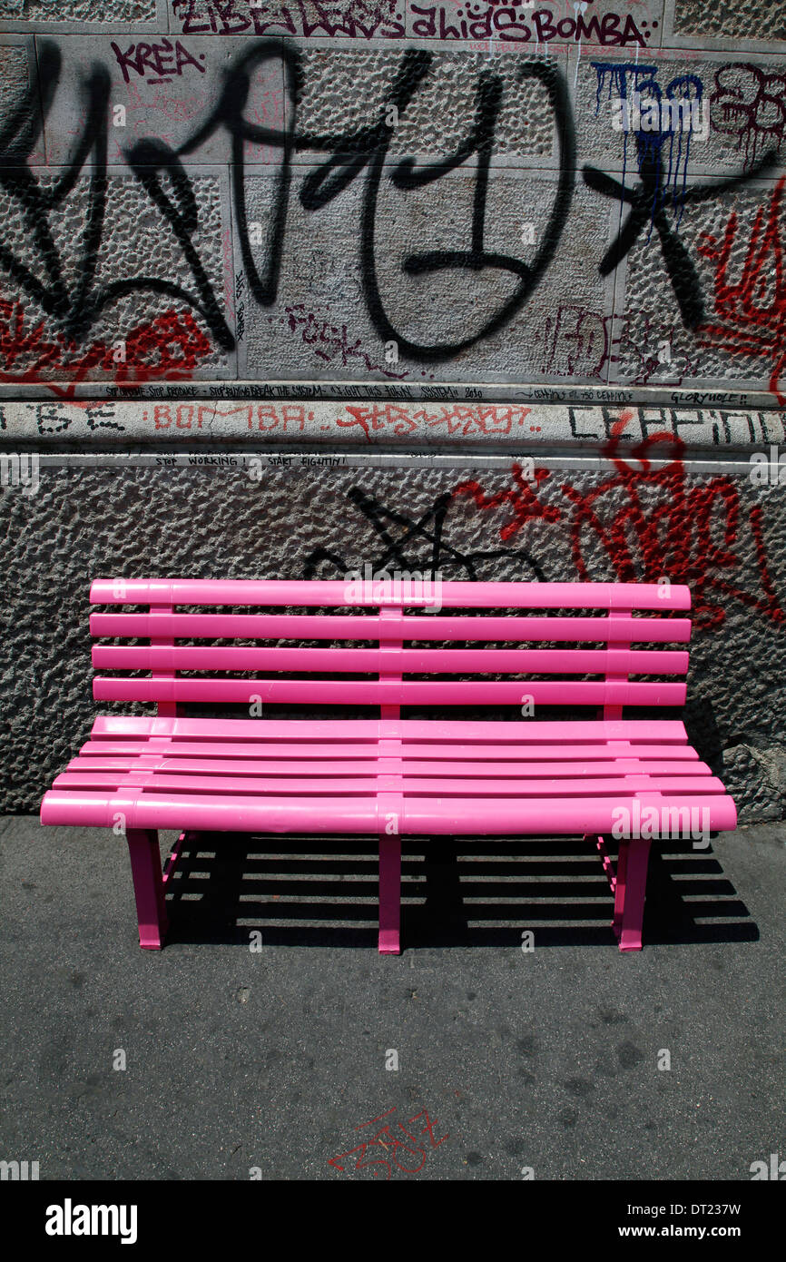 A pink bench on the pavement with urban graffiti on the background - Stock Image