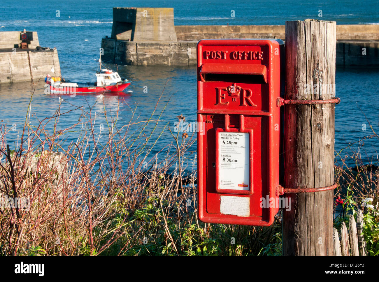 Bright Red British Post Box by the Harbour in the village of Craster, Craster, Northumberland, England, UK - Stock Image