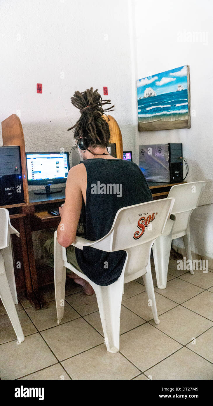young man with dreadlocks piled atop his head sits at public access computer looking at Facebook in internet cafe Zipolite - Stock Image