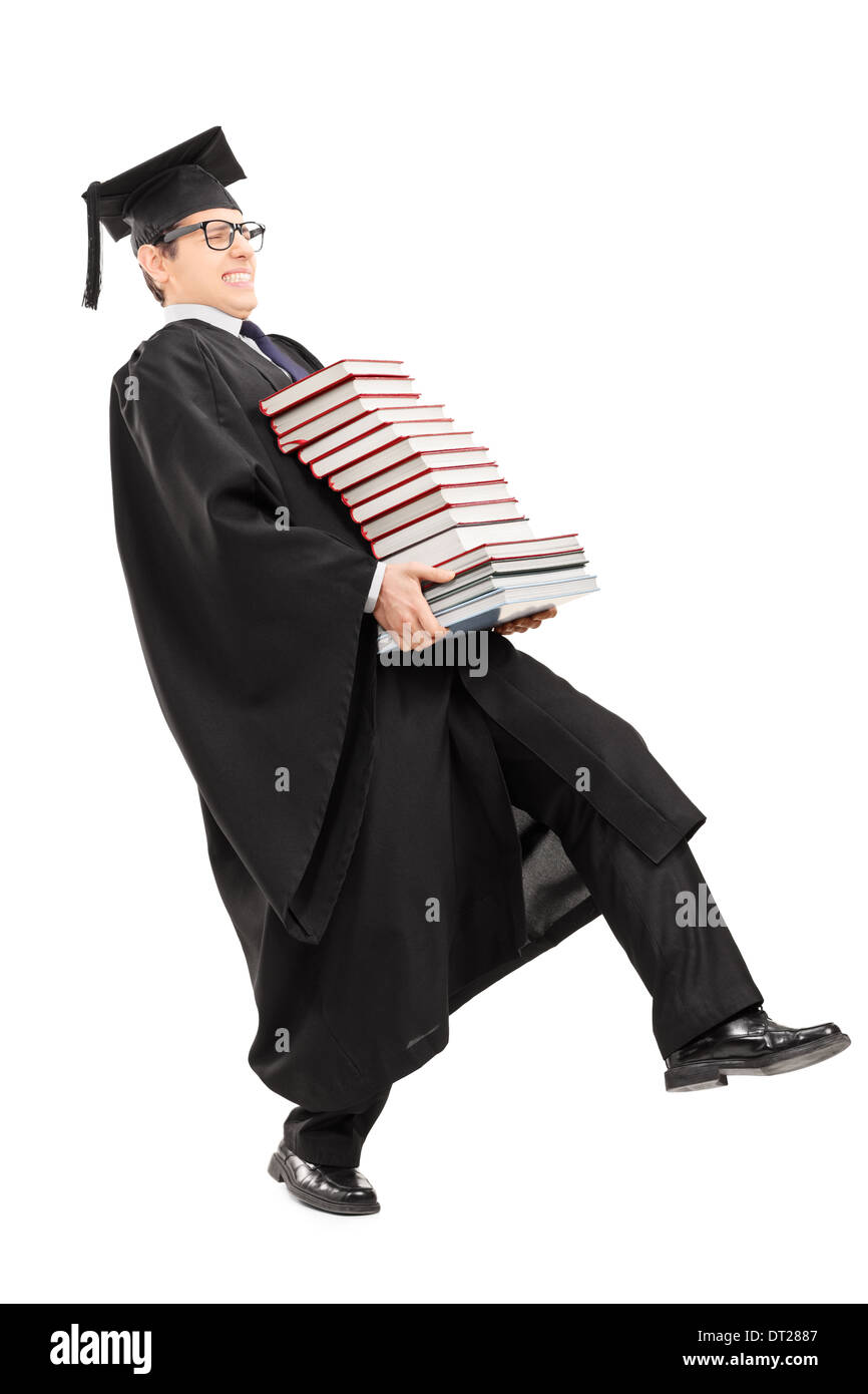 Full length portrait of young man in graduation gown carrying bunch ...