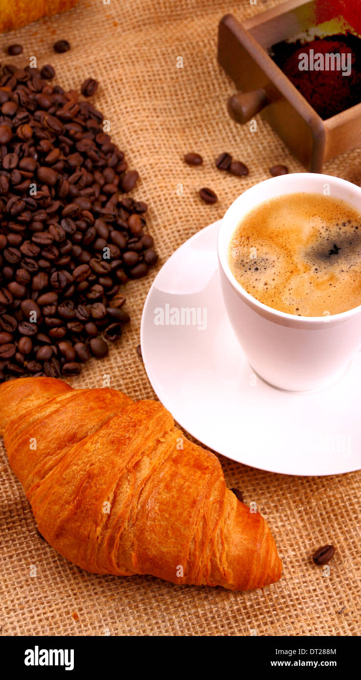 Coffee in white cup and croissant, top view - Stock Image