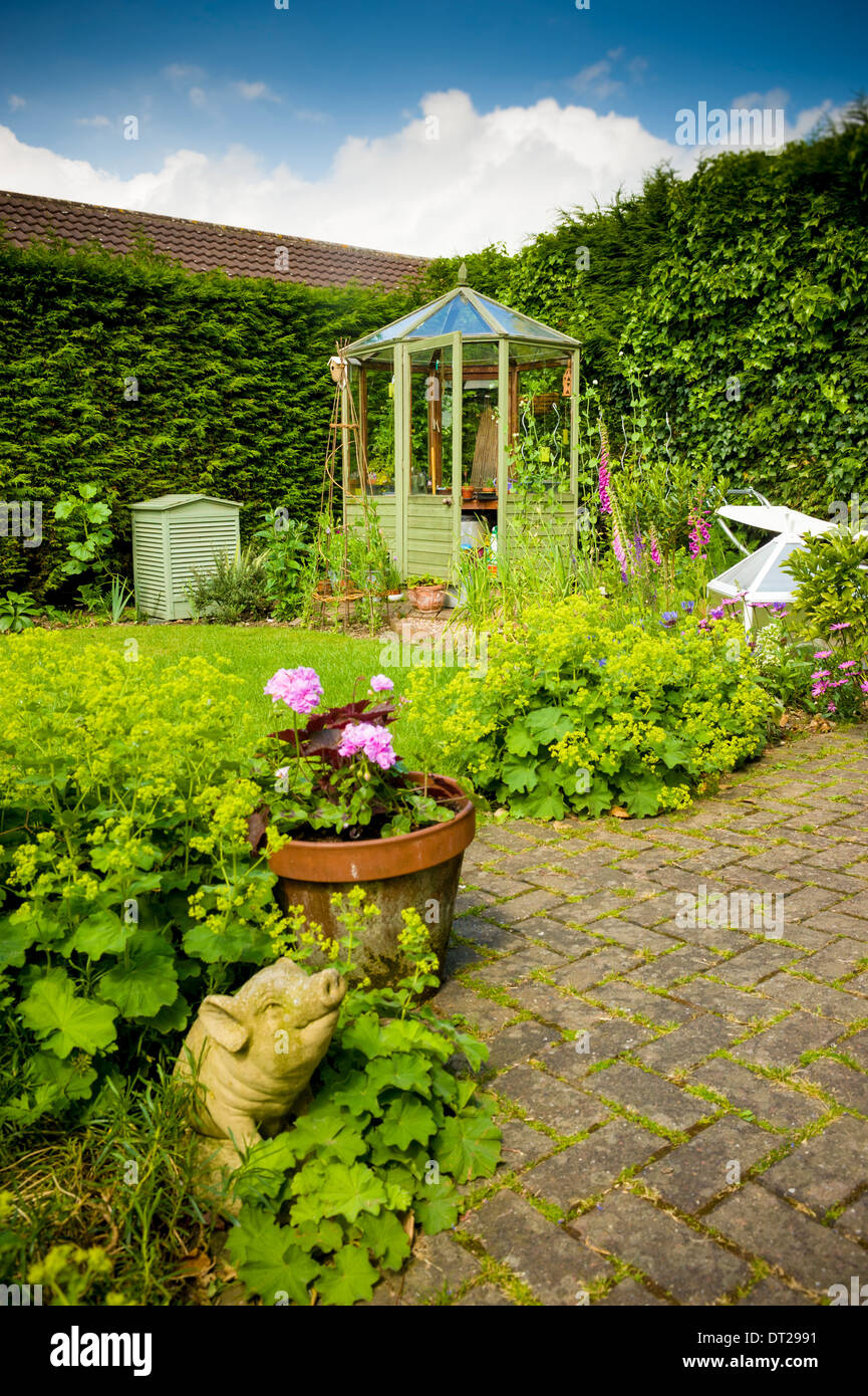 Domestic garden with patio, lawn and greenhouse - Stock Image