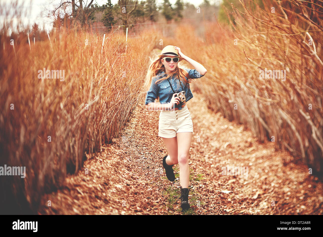 Young woman in fedora hat running towards camera Stock Photo