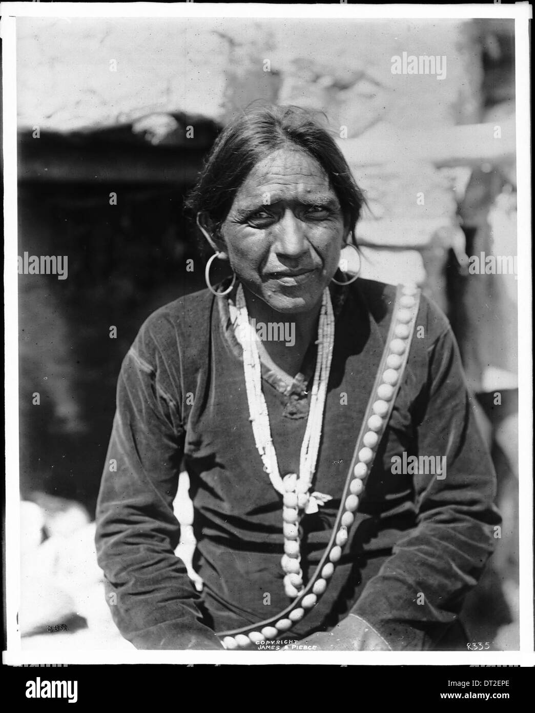 6440becdd Navajo Indian man wearing large silver earrings, and wampum necklace,  ca.1901 -