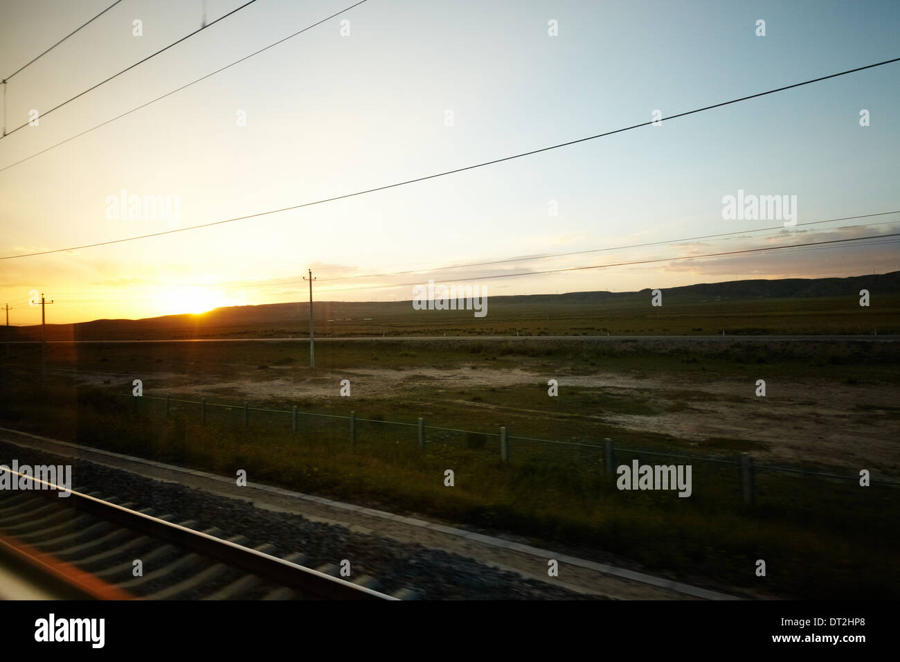 Sunset view of outskirts China on T22 Qinghai Tibet train - Stock Image