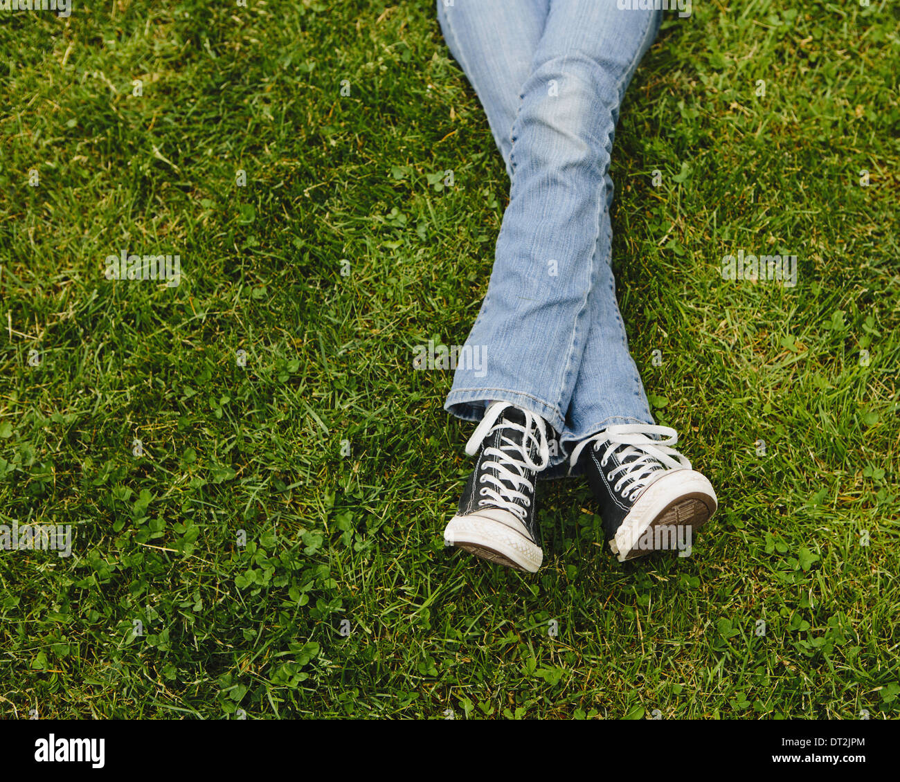 21b1e189a33 Ten year old girl lying on the grass Legs crossed at the ankles - Stock  Image