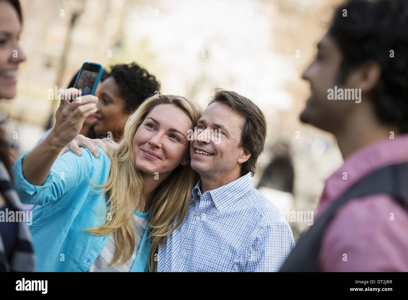 People outdoors in the city in spring time A woman using her cell phone to take a photograph A group of friends men and women - Stock Image