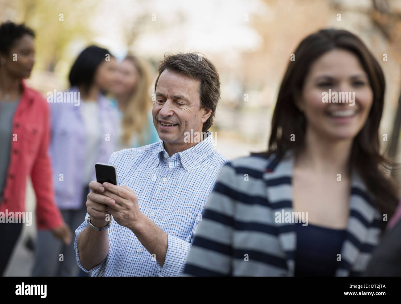 People outdoors in the city in spring time A man checking his cell phone among - Stock Image