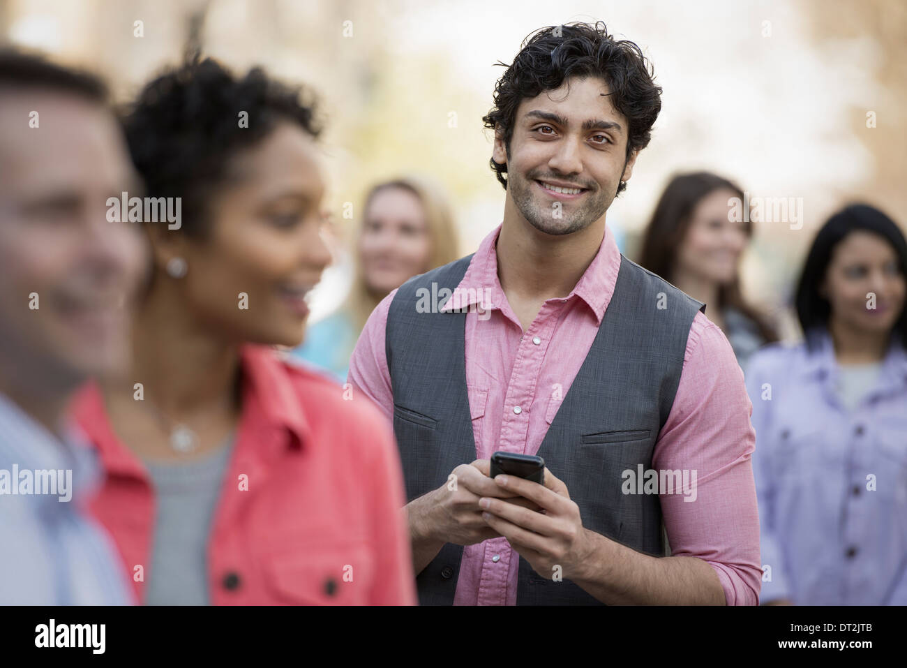park and one young man holding a mobile phone - Stock Image