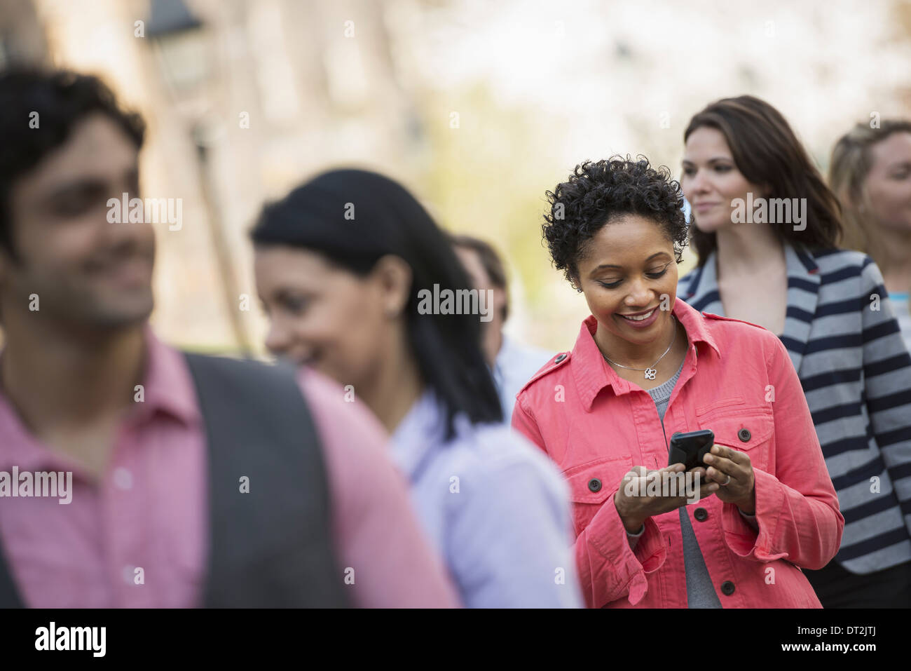People outdoors in the city in spring time A woman standing among a group checking her cell phone - Stock Image