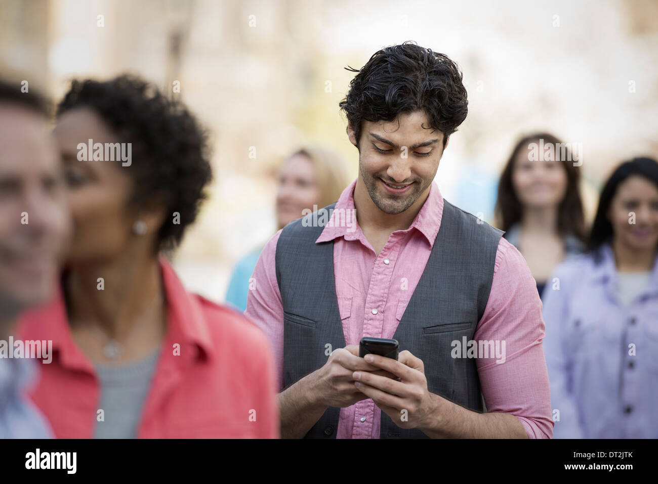 People outdoors in the city in spring time A man looking at his cell phone - Stock Image
