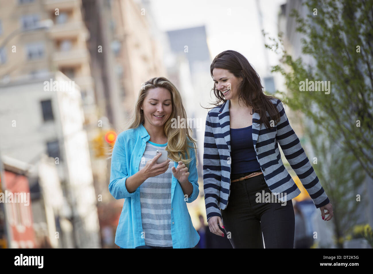 People outdoors in New York city in spring time Two women walking one checking her cell phone - Stock Image