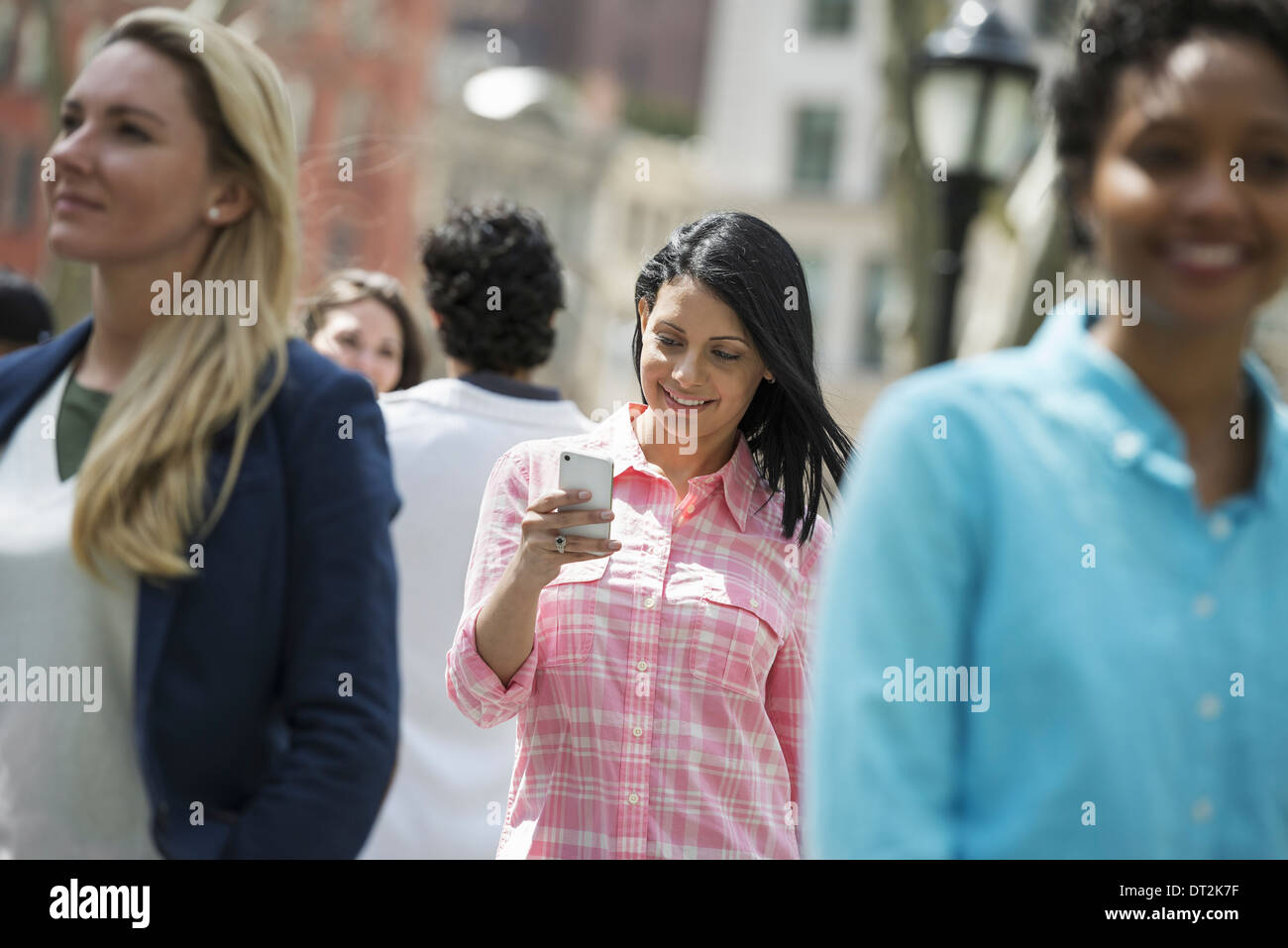 park Three women one checking her mobile phon - Stock Image