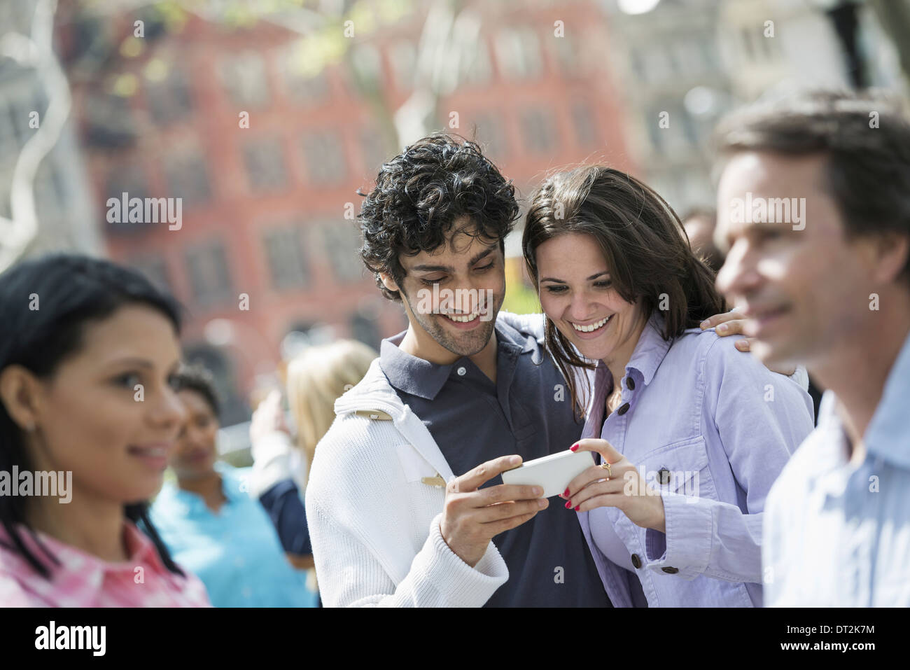 a couple at the centre looking at a cell phone - Stock Image