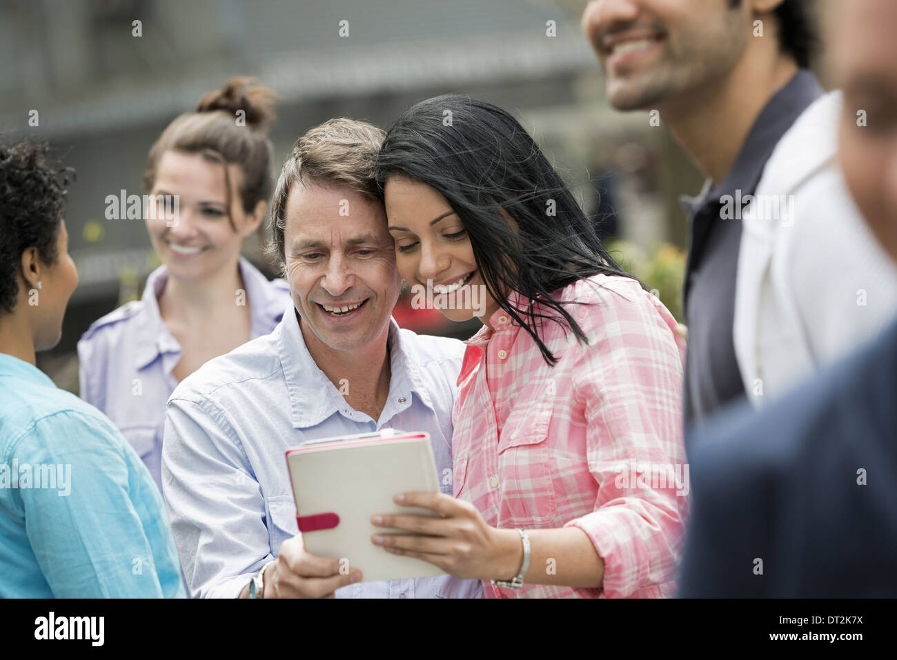 People outdoors spring time New York City a couple in the centre looking at a digital tablet screen Stock Photo