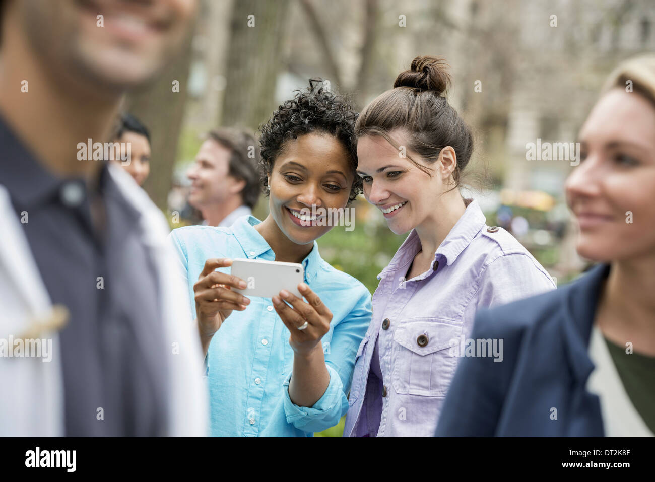 People outdoors in the city spring time New York City park Two women in a group of friends looking at a cell phone and smiling - Stock Image