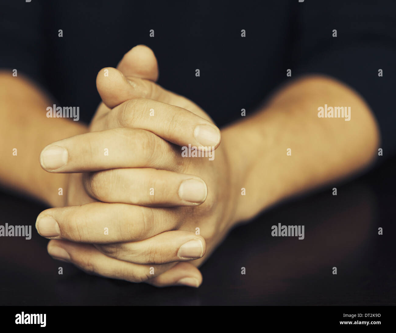 The clasped hands of a man wearing dark coloured clothes Stock Photo