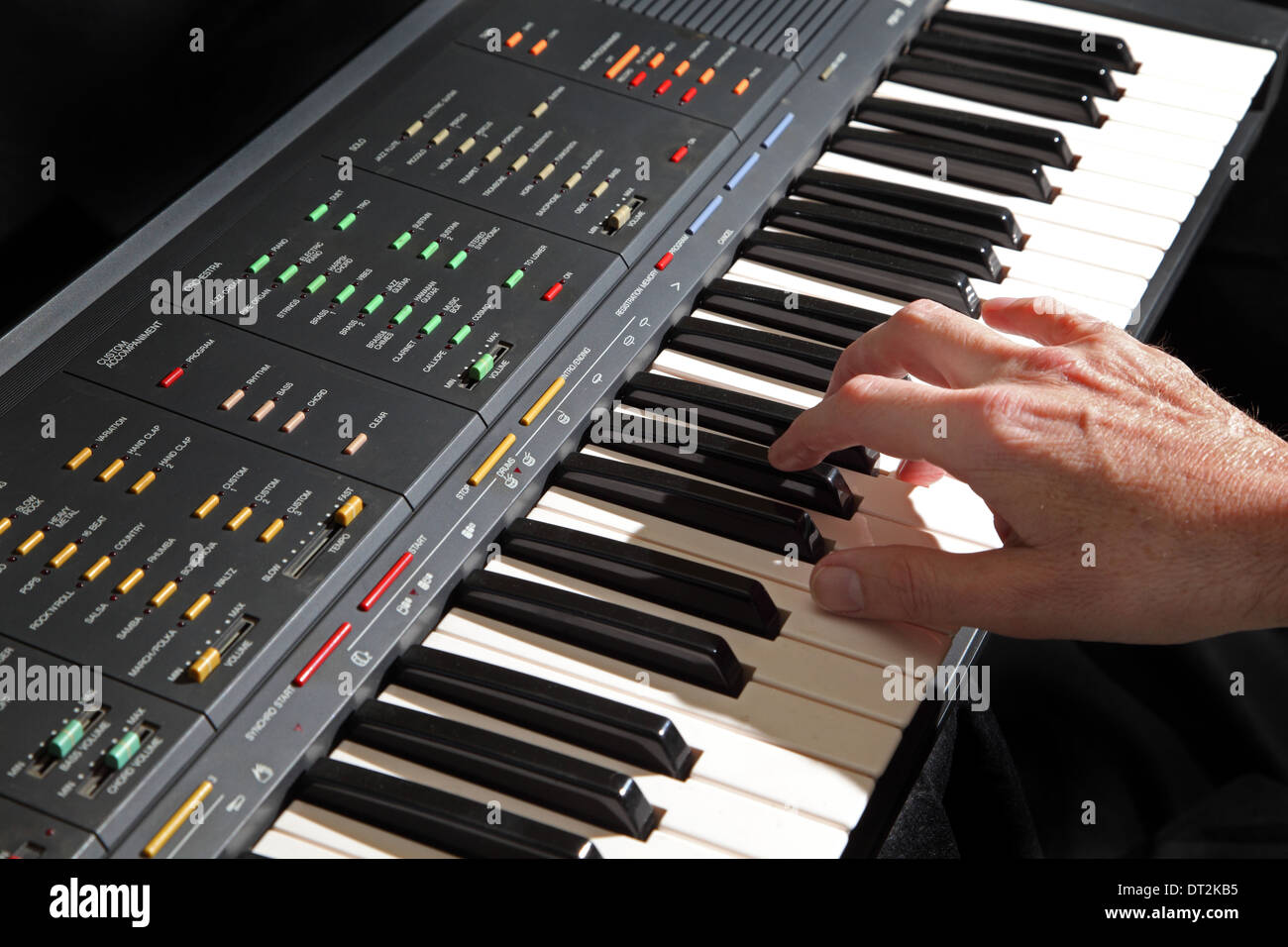 An electronic musical keyboard instrument being played showing the performers right hand. Plain black background. - Stock Image